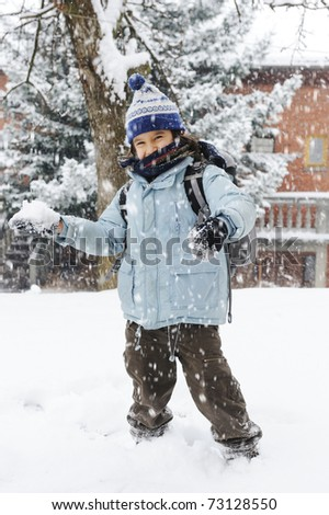 happy schoolboy kid wearing warm clothes in snow on a cold winter day, smiling and joying