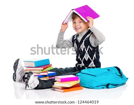 Happy schoolboy sitting on floor with backpack and books isolated on white background