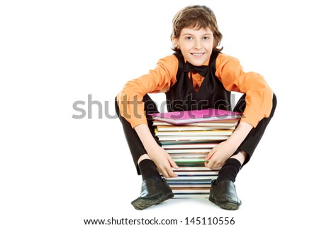 Happy schoolboy sitting with a stack of books. Isolated over white.