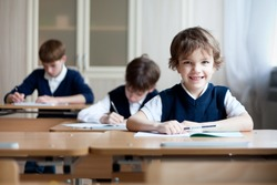 Happy schoolboys sitting at desk, classroom