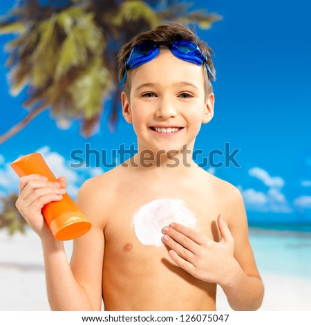 Happy schoolchild boy applying sun block cream on the tanned body.  Boy holding orange sun tan lotion bottle.