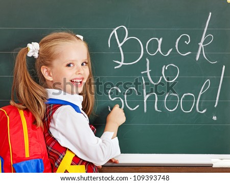 Happy schoolchild writting on blackboard.