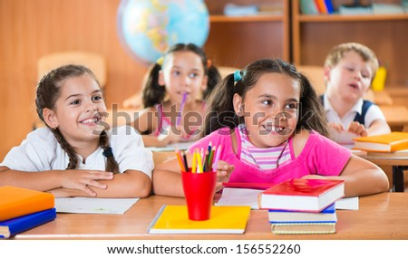 Happy schoolchildren during lesson in classroom at school