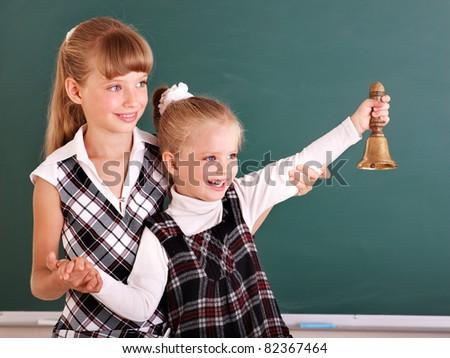 Happy schoolchildren in classroom near blackboard.