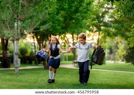 happy schoolchildren running in the park after school. waving backpacks. September 1