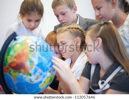 Happy schoolchildrensearching country on the globe