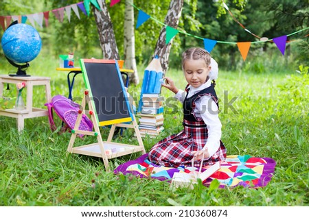 Happy schoolgirl child kid girl sitting on grass reading a book and writing on chalkboard, classroom outdoors, celebration