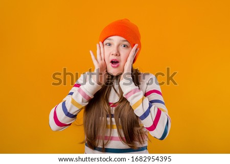 Happy schoolgirl with long hair holds her hands in front on a yellow background