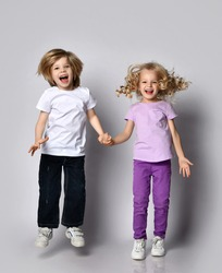 Happy screaming frolic blond kids boy and girl in casual stylish clothes jump together holding hands, having fun play. Happy childhood concept