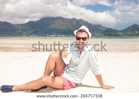 happy seated young man making the ok thumbs up hand sign on the beach