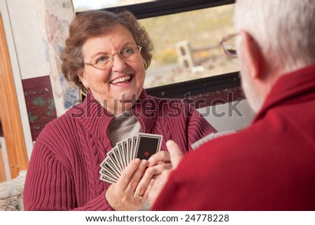 Happy Senior Adult Couple Playing Cards in Their RV. - stock photo