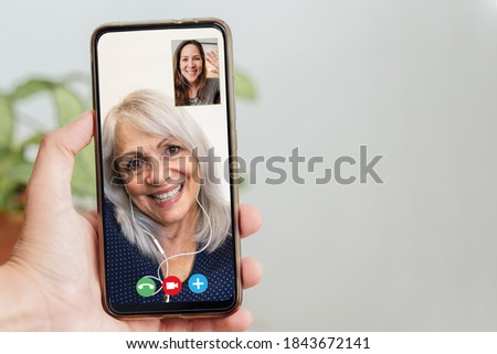 Happy senior and daughter talking on video call with mobile phone during coronavirus outbreak - Online app and social distancing concept