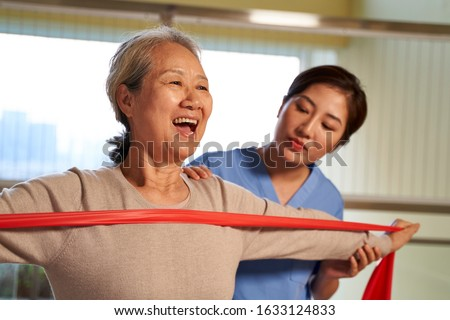 happy senior asian woman exercising using resistance band guided by physical therapist in rehab center