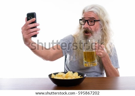 Happy senior bearded man smiling while taking selfie picture with mobile phone while holding glass of beer with bowl of potato chips on wooden table