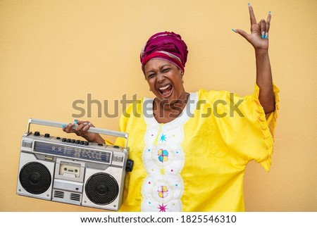 Happy senior black woman with traditional african dress dancing holding vintage stereo - Focus on face Сток-фото ©