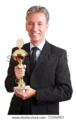 Happy senior business man holding a trophy in his hands