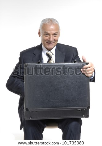 Happy senior businessman opening a suitcase on white background.