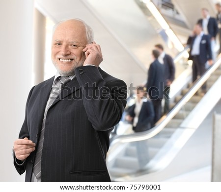 Happy senior businessman standing in office lobby, taking phone call, smiling at camera.?