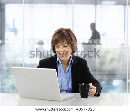 Happy senior businesswoman sitting at desk in  modern corporate office, using laptop and drinking coffee.