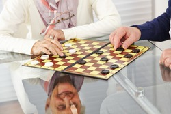 Happy senior citizen couple playing checkers at home