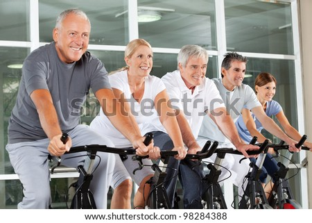 Happy senior citizens exercising in class in fitness center