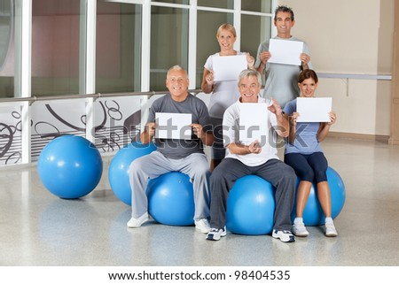 Happy senior citizens on gym balls holding empty signs in fitness center