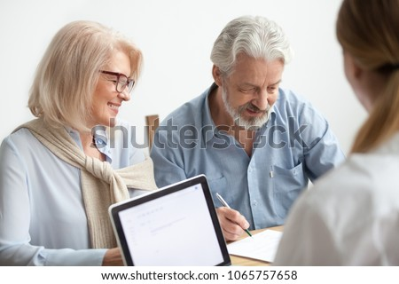 Happy senior couple about to sign document at meeting with financial advisor, older man agrees to put signature on contract making investment purchase, taking insurance, aged family in travel office