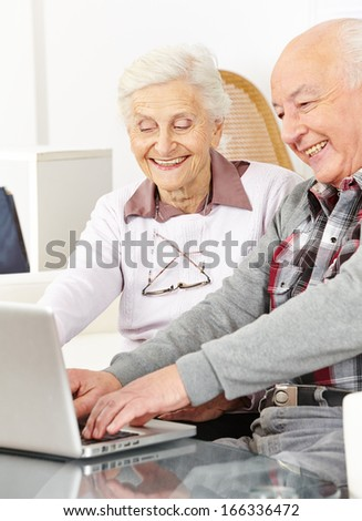 Happy senior couple chatting over internet with laptop computer