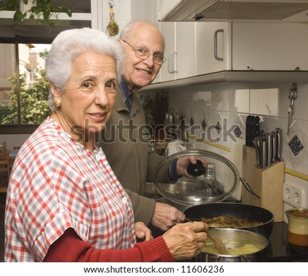 Happy senior couple cooking at home