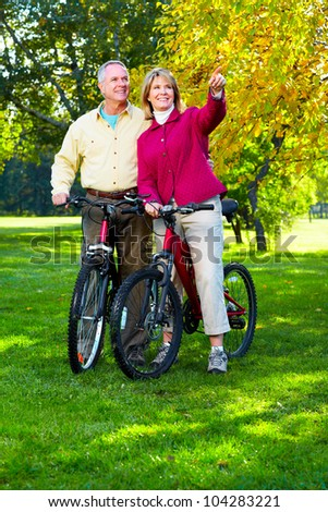 Happy Senior couple cycling in the park.