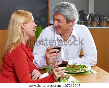 Happy senior couple dining together with wine in a restaurant