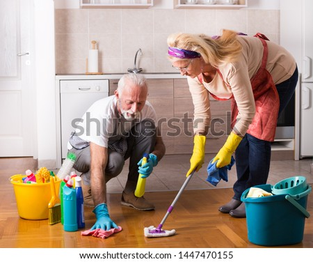 Happy senior couple doing chores together on floor #1447470155