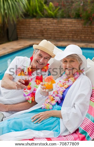 Happy senior couple drinking cocktails and toasting each other