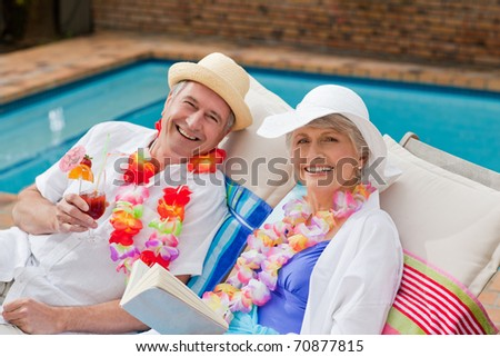 Happy senior couple drinking cocktails and toasting each other - stock photo