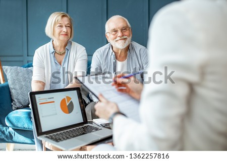Happy senior couple during the meeting with agent or financial consultant, signing some agreement in the comfortable office
