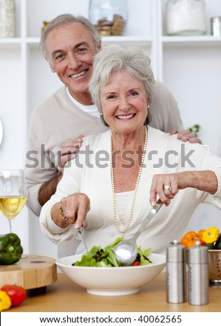 Happy senior couple eeating a salad in the kitchen and drinkng wine