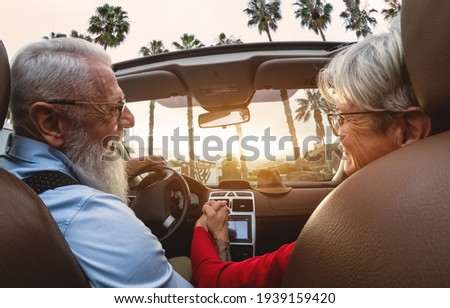 Happy senior couple having fun driving on new convertible car - Mature people enjoying time together during road trip tour vacation - Elderly lifestyle and travel culture transportation concept