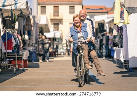 Happy senior couple having fun with bicycle at flea market - Concept of active playful elderly with bike during retirement - Everyday joy lifestyle without age limitation in a spring sunny afternoon