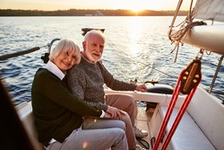 Happy senior couple in love, elderly man and woman holding hands, hugging and spending time together while sitting on the side of yacht deck floating in sea on a sunny day