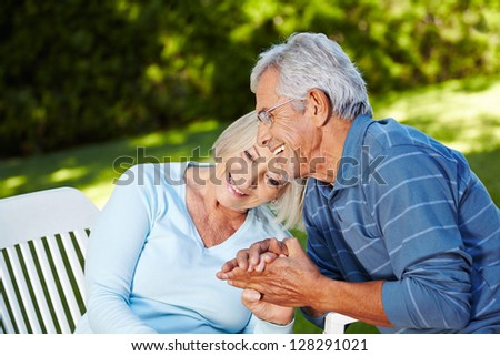 Happy senior couple in love sitting outside in a garden