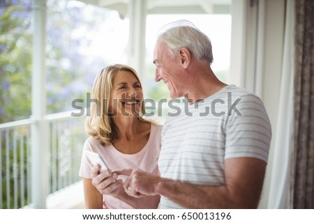 Happy senior couple interacting with each other in balcony at home