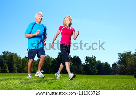 Happy senior couple jogging in the park.