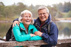 Happy senior couple leaning on a wooden fence laughing to camera, close up, Lake District, UK