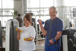 Happy senior couple lifting dumbbells at gym. Strength and power training for older adults.