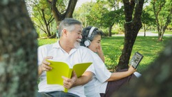 happy senior couple listening to earphone with digital tablet and read book relax in park, People lifestyle concept.