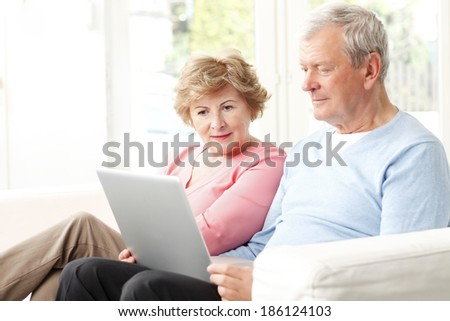 Happy senior couple planning for retirement at home. They surfing on internet with laptop