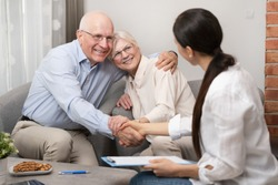 Happy senior couple planning their investments with financial advisor. Deal agreement, signed contract with handshake concept