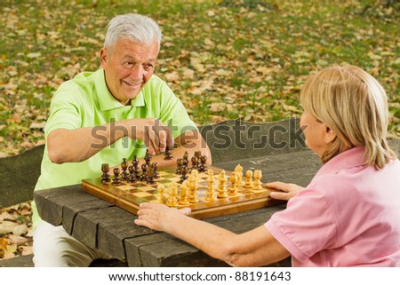 Happy senior couple playing chess on a park bench.