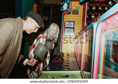 Happy senior couple playing whack a mole at a game arcade Stockfoto ©
