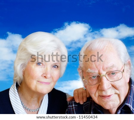 Happy senior couple portrait on sky background